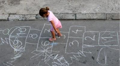 Petite fille jouant à la marelle