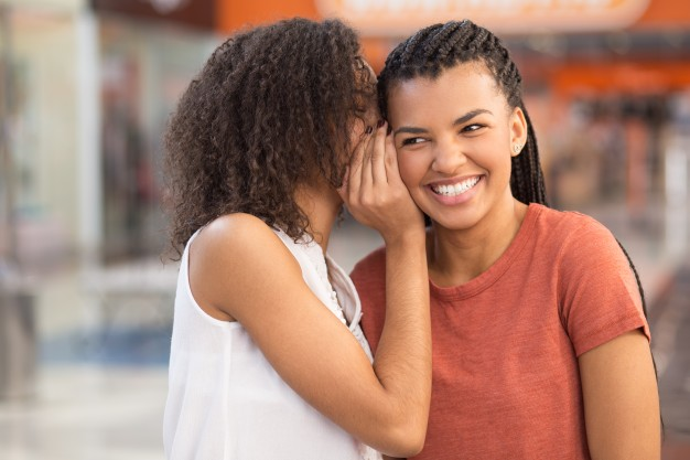 black-girl-whispering-secret-to-smiling-girlfriend_1262-3456